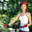 Portrait of happy young woman with mountain bike outdoors. — Stock Photo #48925643