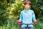 Portrait of happy young woman riding mountain bike. — Stock Photo