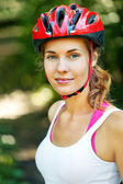 Portrait of happy young cyclist in sport clothes and helmet. — Stock Photo