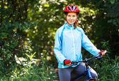 Portrait of happy young woman with mountain bike outdoors. — Stock Photo