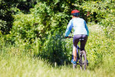 Young woman with mountain bike outdoors. — Stok fotoğraf