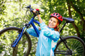 Portrait of young woman with mountain bike on shoulder. — Stock Photo