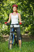 Portrait of happy young woman with mountain bike outdoors. — Foto de Stock