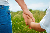 Mother holding hand of her son outdoors — Stock Photo