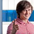 Young guy gesturing with a YOU sign against the window — Stock Photo #5740814