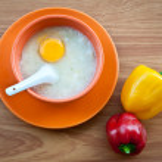 Rice porridge with egg in orange bowl. — Stock Photo #19008929