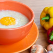 Rice porridge with egg in orange bowl. — Stock Photo