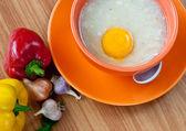 Rice porridge with egg in orange bowl. — Stock Photo