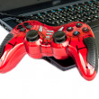 Stock Photo: Red joystick game controller on laptop .