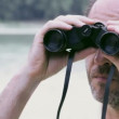 Man watching the nature through binoculars - Stock Photo