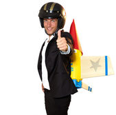 Young businessman with rocket on his back and thumb up — Stock Photo