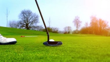Close-up of golfer using putter to sink putt to hole — Stock Video