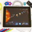 Stock Photo: Planets on Ipad 3 with school accesories