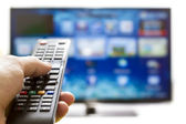 Smart tv and hand pressing remote control — Stock Photo