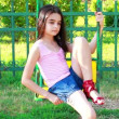 Sad young girl on swing - Stock fotografie
