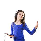 Smiling teenage girl listening music on digital tablet — Stock Photo