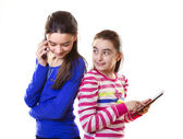 Happy teen girls with digital tablet and smartphone — Stockfoto