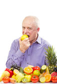 Senior man eating a green apple — Stock Photo