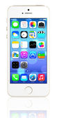 Gold iPhone 5s showing the home screen with iOS7. — Stock Photo