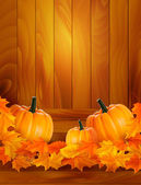 Pumpkins on wooden background with leaves Autumn background Vector — Stock vektor