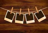 Rétro photos suspendu à une corde sur un fond en bois sombre. vector. — Vecteur