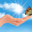 Stock Vector: Hand holding a butterfly against a blue sky and sun. Vector illu