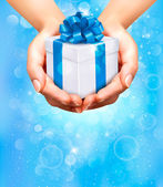 Holiday background with hands holding gift boxes. Concept of giving presents. — Stockvektor