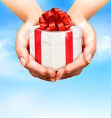 Sfondo vacanza con mani tenendo scatole regalo. concetto di giv — Vettoriale Stock