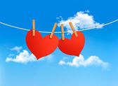 Two hearts hanging on a rope in front of a sky. Valentine's day — Stock Vector