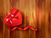 Red heart-shaped gift box with ribbon on wooden background. Vect — Stock Vector