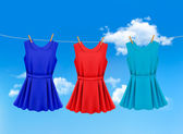 Set of colored dresses hanging on a clothesline on a sunny day.  — Stock Vector