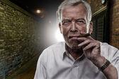 Senior man smoking a cigar — Stock Photo