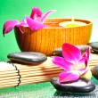 Image of spa therapy, flowers in water and a bamboo mat. — Stockfoto
