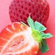 Ripen strawberry over red background — Stock Photo
