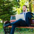 Young business man working with laptop and cellphone — Stock Photo #13705679