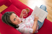 Young woman relaxing and reading a book — Stockfoto
