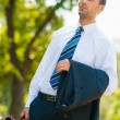 Young business man walking in the park — Stock Photo