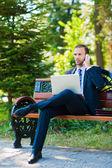 Feliz sorridente negócios jovem trabalhando com laptop e cellpho — Foto Stock