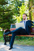 Jeune homme d'affaires souriant heureux travail avec ordinateur portable et cellpho — Photo