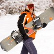 Young girl holding a snowboard in wood — Stock Photo