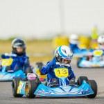 Постер, плакат: Kart pilots competing