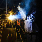 Welder with protective mask welding metal and sparks — Foto Stock