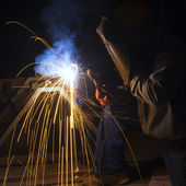 Welder with protective mask welding metal and sparks — Stock Photo