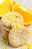 Cookies and orange fruit on wood background — Stock Photo