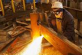 Saldatore con maschera protettiva in metallo e scintille di saldatura — Foto Stock