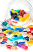 Colored pills, tablets and capsules on a white background — Stock Photo