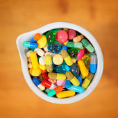 Bowl of multicolored tablets and capsules — Stock Photo