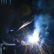 Welder with protective mask welding metal and sparks — Stock Photo #34683041