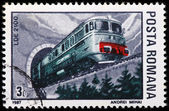 A stamp printed in Romania shows a train on rails — Stok fotoğraf