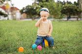 Niño sentado sobre la verde hierba — Foto de Stock